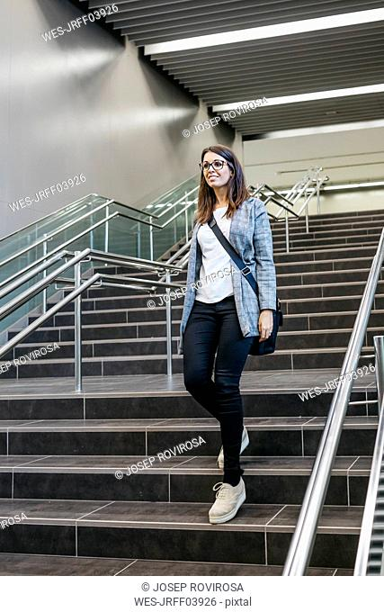 Woman going down some stairs of a subway station, to go to work