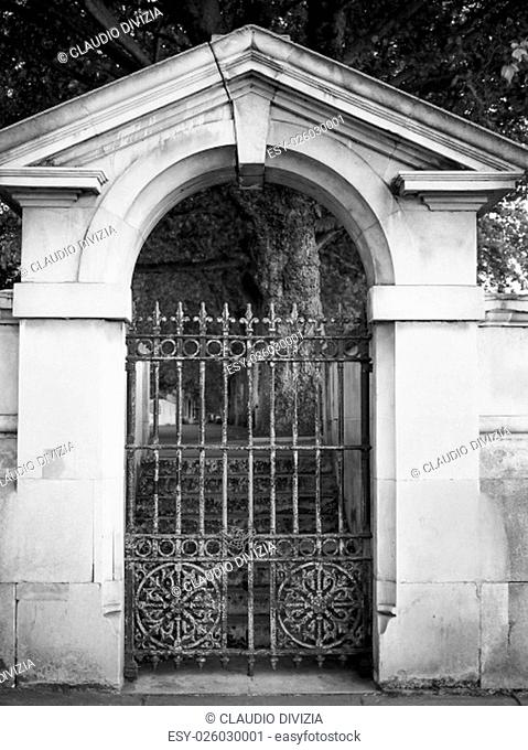 Old iron gate under a marble arch in black and white