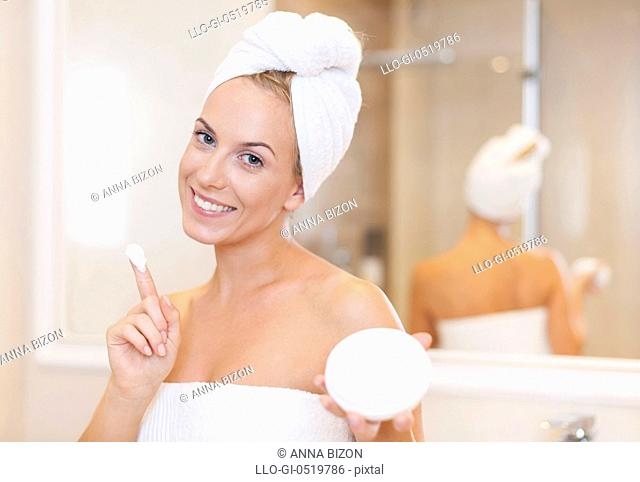 Woman moisturizing face after the shower. Debica, Poland&#10