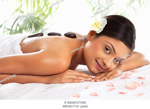 Portrait of young woman getting lastone treatment