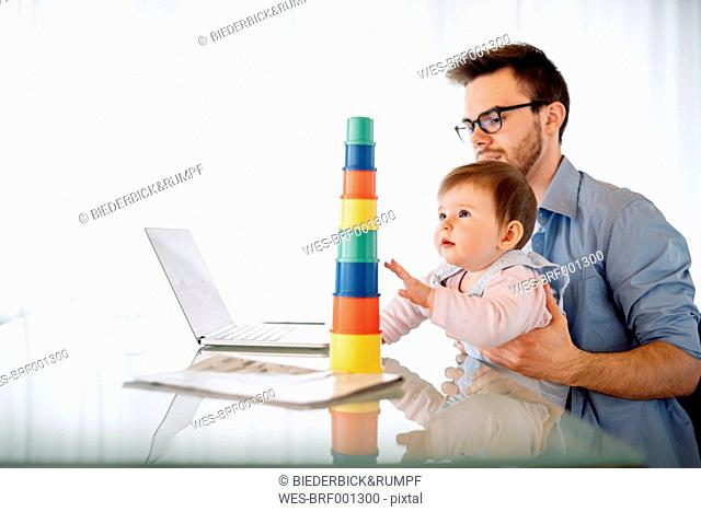 Young man with baby girl on his lap sitting at desk