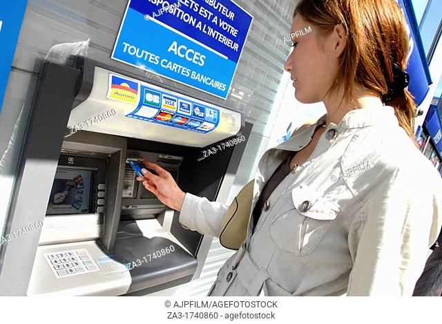 20 years old woman taking cash at a cash point