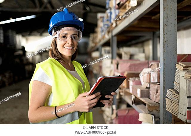 Woman taking stock in warehouse of construction company