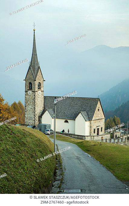 Autumn evening at San Lorenzo church in the alpine village of Sauris di Sopra, Udine, Italy. Dolomites