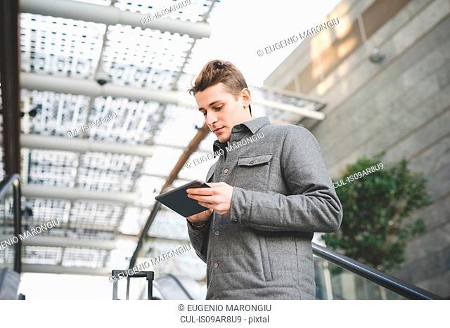Portrait of young businessman commuter using digital tablet