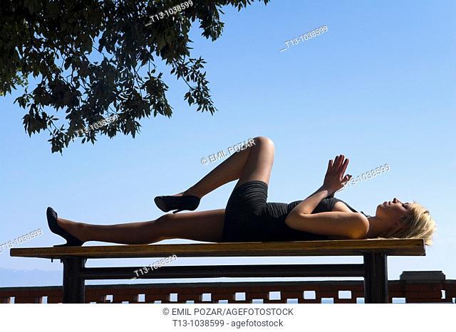 Lying on a park bench pretty woman body silhouette