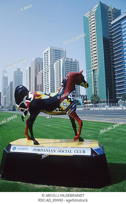 Tower blocks and sculpture of multicolored horse Sheikh Zayed Road Dubai United Arab Emirates