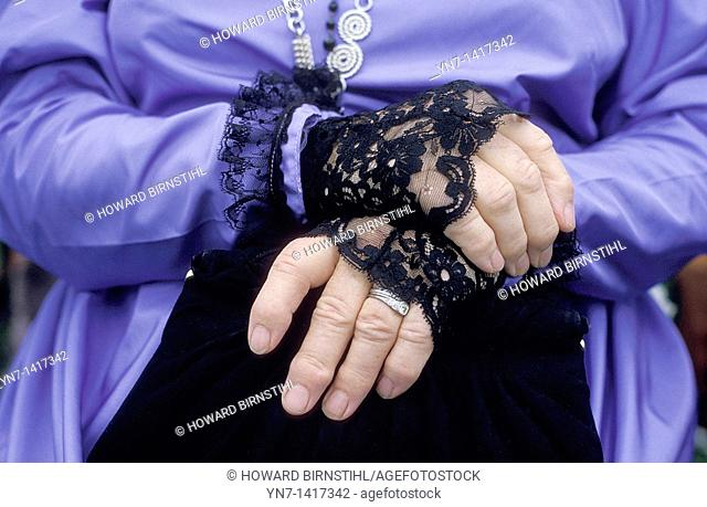 Close up of a middle aged woman's hands folded in repose, her costume that of the middle eighteen hundreds featuring black lace cuffs