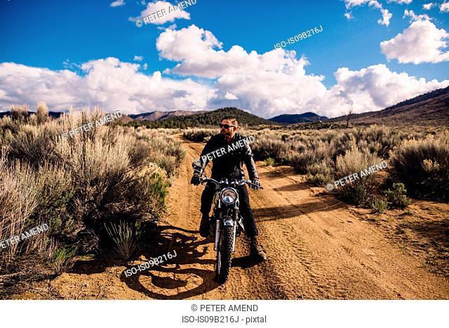 Motorcyclist sitting on motorbike looking away, Kennedy Meadows, California, USA