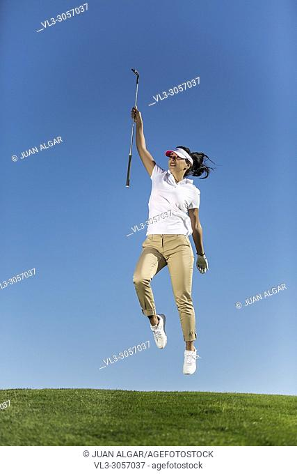 Excited elegant woman holding golf driver and jumping up high on blue sky background