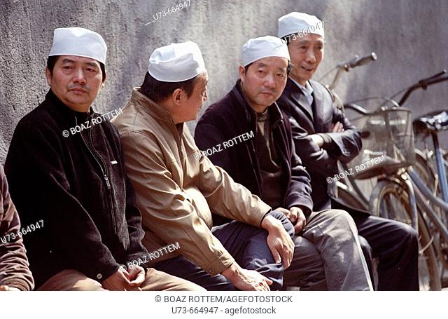 Muslim men sit and relax in the grounds of the beautiful old mosque in the old city of Xian, China