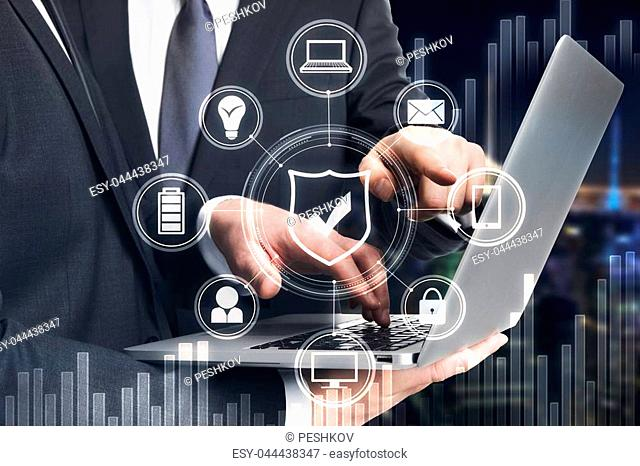 Businessmen pointing at laptop with business hologram on blurry night city background. Finance, teamwork and communication concept. Double exposure