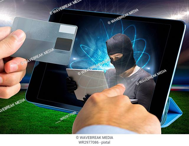 Close up of hand touching a tablet with hacker and holding credit card