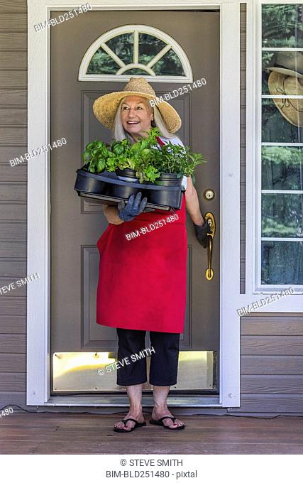 Caucasian woman holding potted plants in doorway