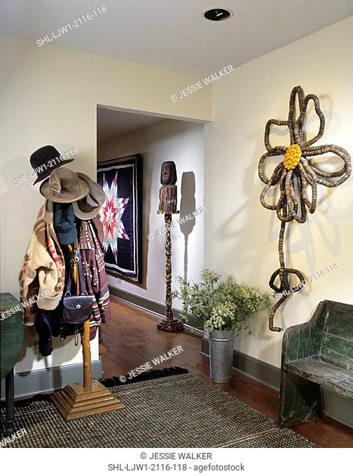 ENTRY HALL: Bottlecap sculpture flower, folk art carving, antique quilt on the wall, weathered antique bench and table, coat rack