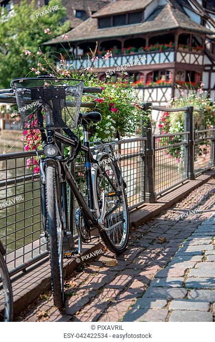 Black bicycle attached to metal gate railing on a city street, France, Strasbourg