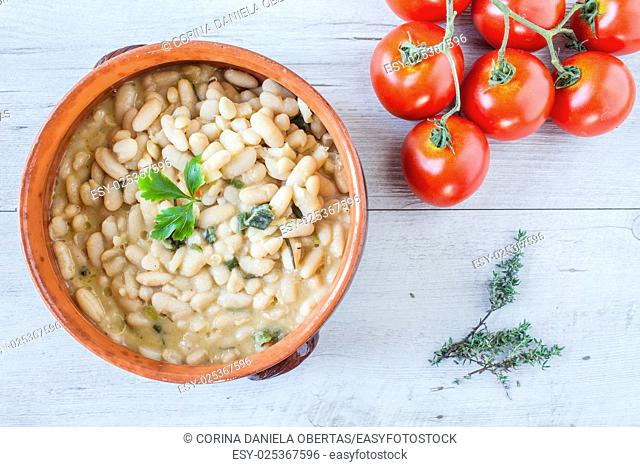 Top view of ceramic bowl with cooked white beans and fresh tomatoes
