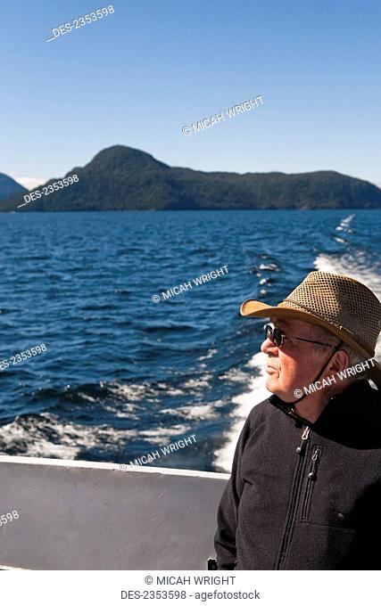 A traveler enjoys a ferry ride across Lake Manapouri in Doubtful Sound; Manapouri, New Zealand