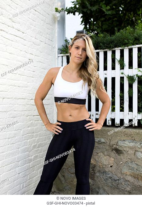 Young Adult Woman in Fitness Attire with Hands on Hips Looking at Camera