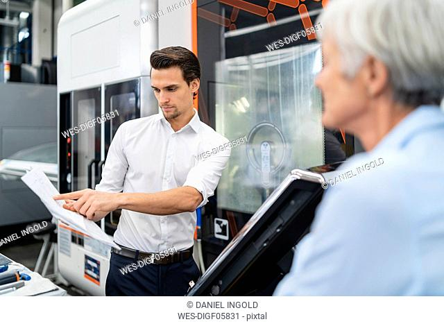 Businessman and senior businesswoman with manual at a machine in a factory