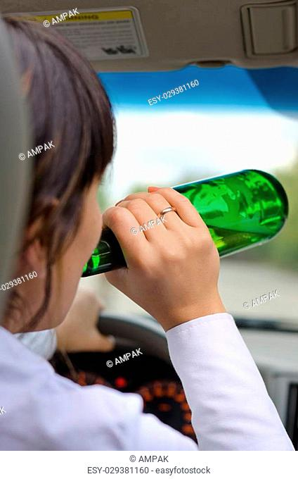 Close up view from behind of an alcoholic woman driver drinking while driving on a road with the bottle of alcohol upended to her lips