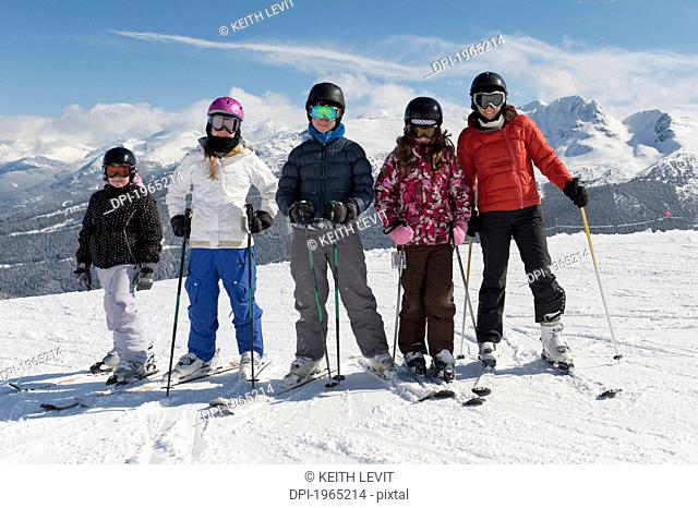 a group of skiers posing with the mountains in the background, whistler british columbia canada