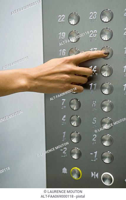 Woman's hand pressing 17 floor button