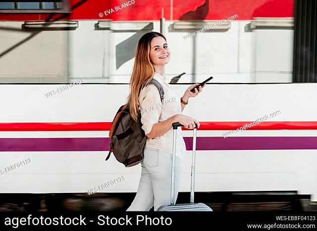Smiling young woman wearing backpack walking with wheeled luggage at railroad station