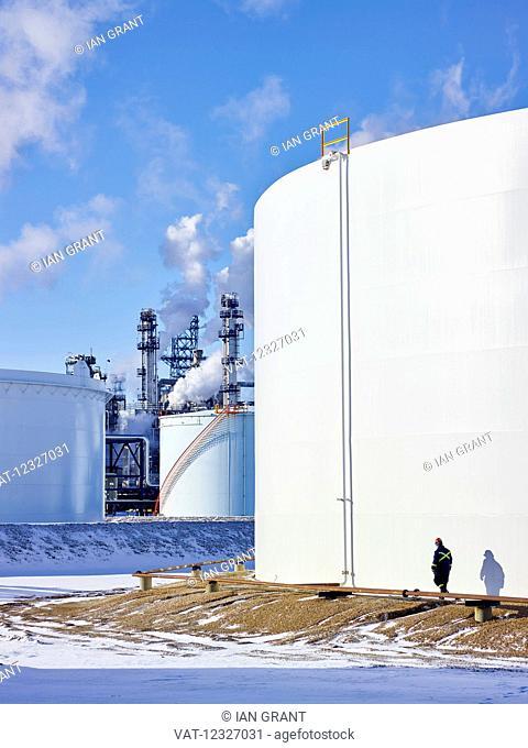 Tradesman working at a large, white storage tank; Edmonton, Alberta, Canada