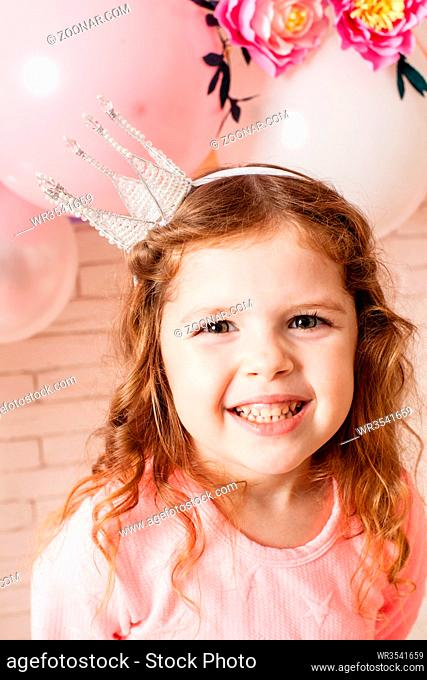 The beautiful little girl with crown over pink girly balloon and paper flower decorations. Little princess is celebrating