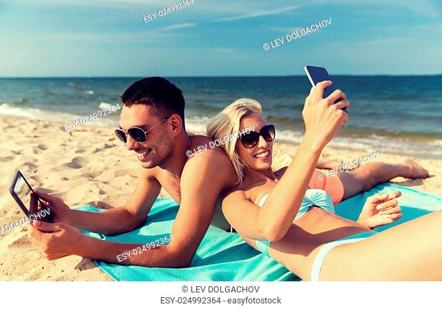 love, travel, tourism, technology and people concept - happy couple on vacation with tablet pc computer and smartphone sunbathing on summer beach
