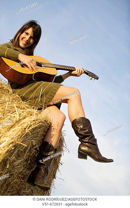 Young woman playing guitar in the countryside