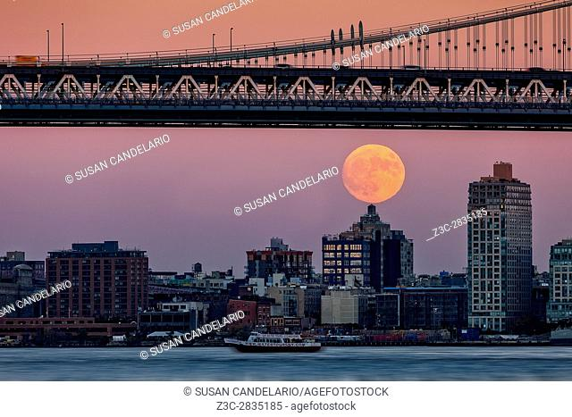 Super Moon Over Manhattan NYC - A view to the Manhattan Bridge with the super moon rising. The supermoon was a show stopper even for a Water Tours NY boat on...