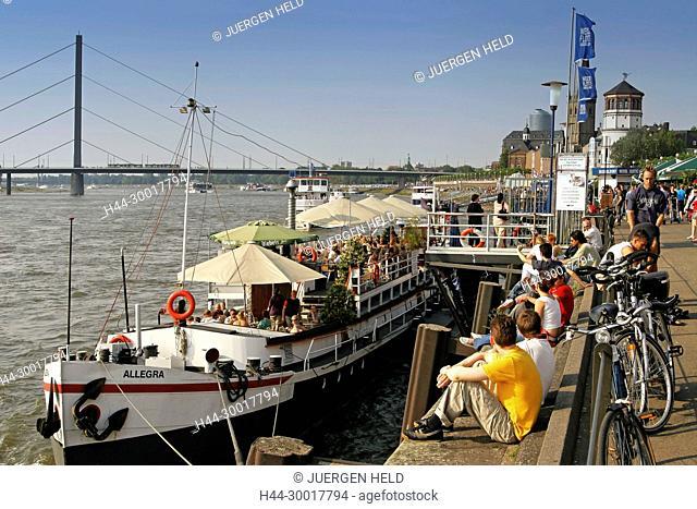 Germany, Duesseldorf, North Rhine-Westphalia, Duesseldorf, Rheinkniebruecke, river rhine, Promenade at river Rhein Cafe on boats deck