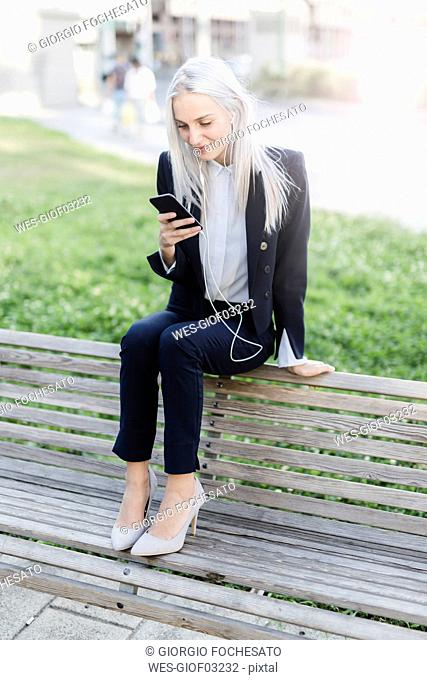 Young businesswoman sitting on bench with cell phone and earphones