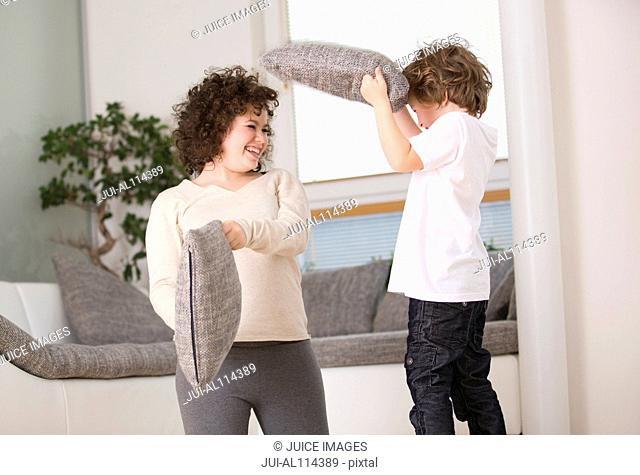 teenage girl and brother having pillow fight