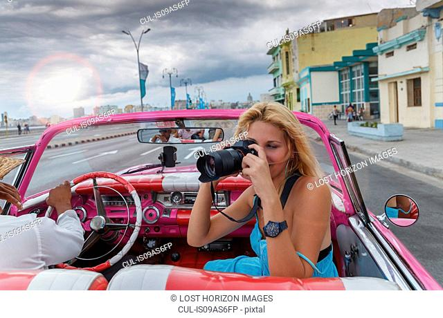 Young woman photographing from a vintage car on the Havana' Malecon, Cuba
