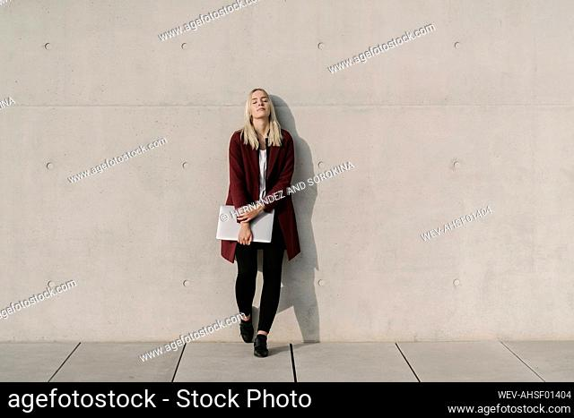 Blond businesswoman with laptop leaning on wall with closed eyes