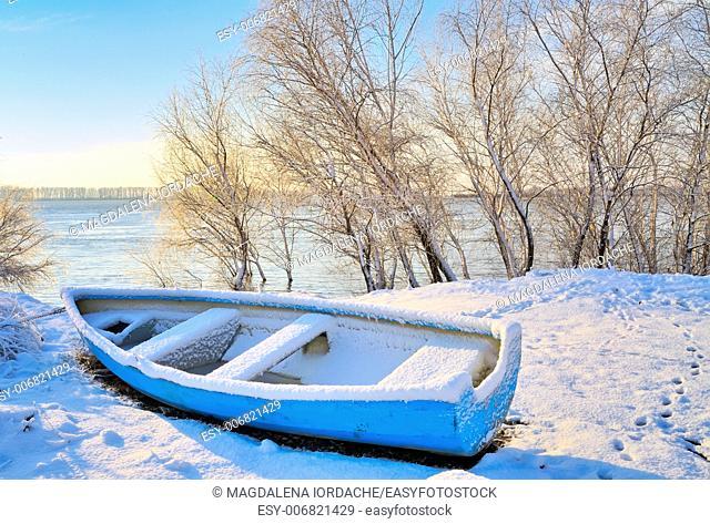 blue boat near danube river in winter time
