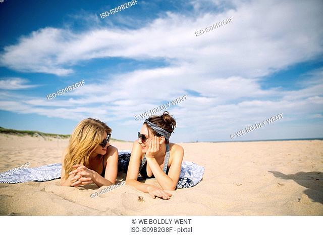 Women relaxing and laying on beach, Amagansett, New York, USA