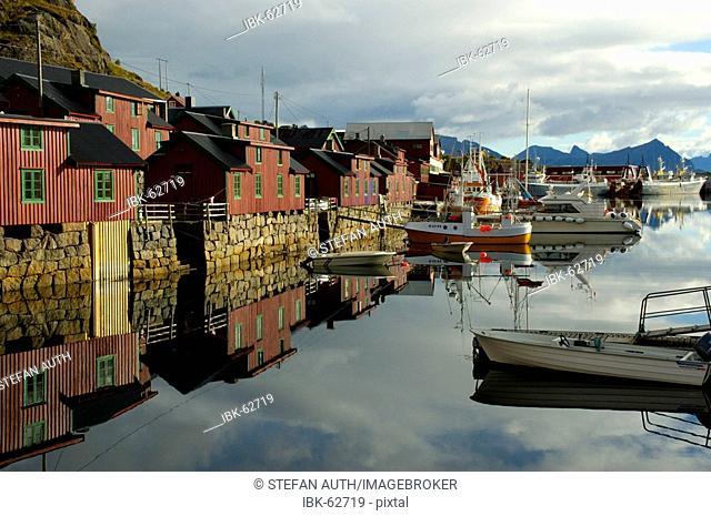 Red painted wooden houses mirror in the water Stamsund Vestvagoya Lofoten Norway