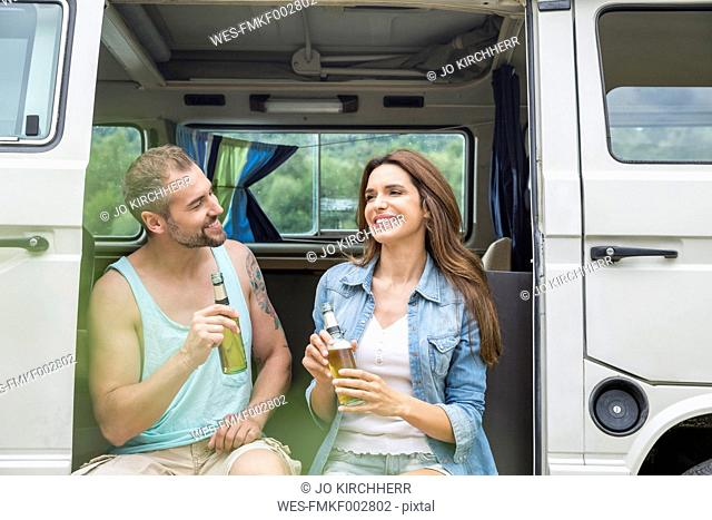 Smiling couple with beer bottles in a van