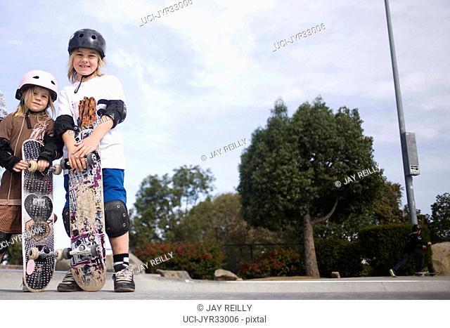 Children in helmets with skateboards in skate park