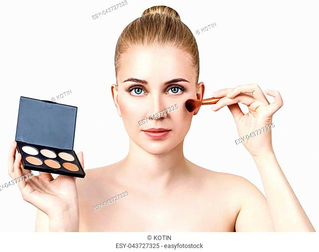 Portrait of lovely girl holding palette for contouring face. Isolated on white background