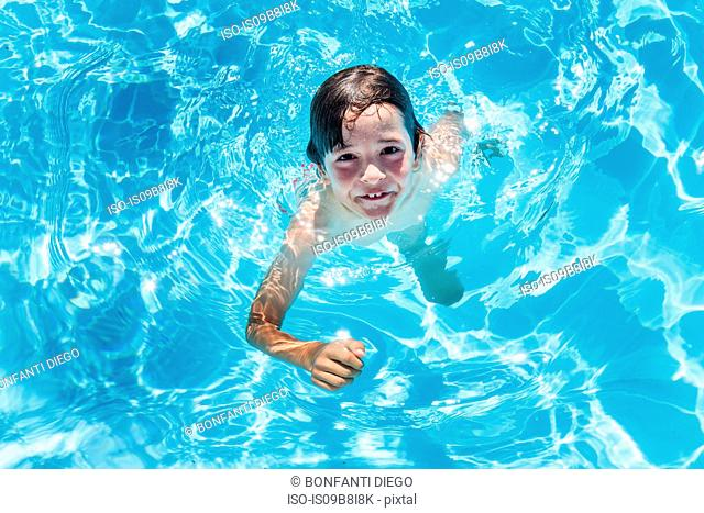 Overhead portrait of boy treading water in outdoor sunlit swimming pool