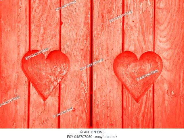 Close up two heart shaped elements, symbol of love, romance and togetherness, wood carved cut in wooden planks texture background