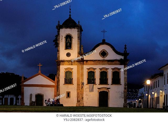 A group of four senior tourists enjoying the nighfall at Paraty's oldest church, the Nossa Senhora dos Pardos Libertos (built 1722); Paraty, Espirito Santo