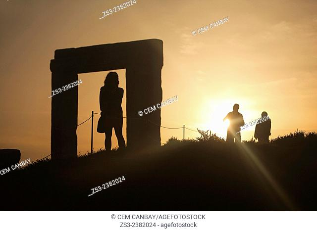 Silhouettes of the tourists at the famous Portara, unfinished door of Apollon Temple, in town center at sunset, Naxos, Cyclades Islands, Greek Islands, Greece