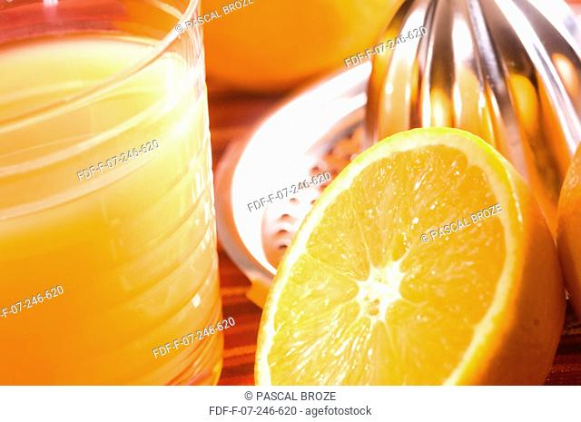 Close-up of a juicer with an orange slice and a glass of orange juice