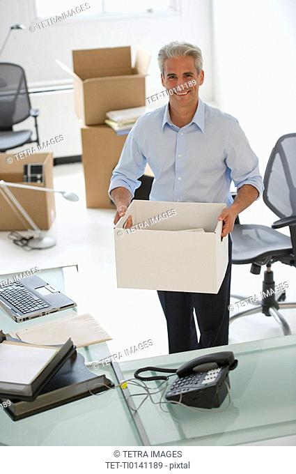Businessman holding a box in his new office
